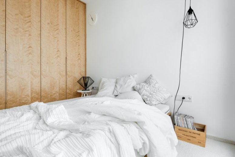 The mster bedroom is decorated simply, with a large bed, a nighstand and a crate with magazines