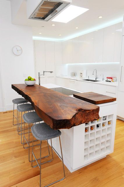 a bold kitchen countertop on a kitchen island with a piece of raw edge wood and wine storage