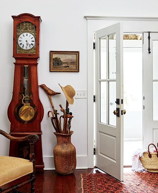a chic entryway with a red wood clock, a wicker vase for umbrellas and a refined chair