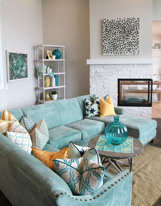 a neutral room is spruced up with a gorgeous aqua sectional sofa and accessories