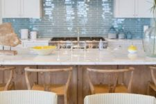 08 a seaside kitchen is made up using matte white cabinets and a glossy blue tile backsplash
