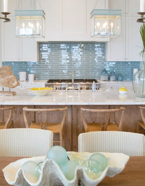 a seaside kitchen is made up using matte white cabinets and a glossy blue tile backsplash
