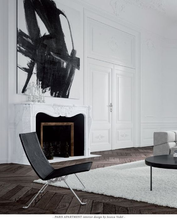 a white marble clad fireplace with black inside and some figures for an artistic feel