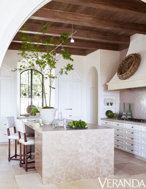 Spanish inspired ktichen in soft shades, with tiles and a rough wood ceiling with beams, a wicker basket on the hood