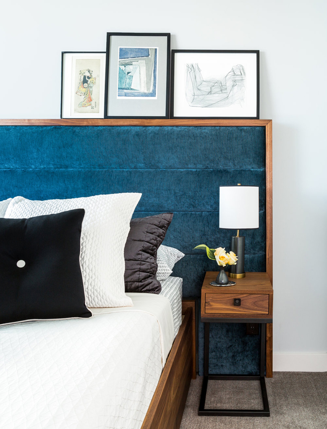 The bedroom has a large bed with an upholstered headboard and lots of artworks