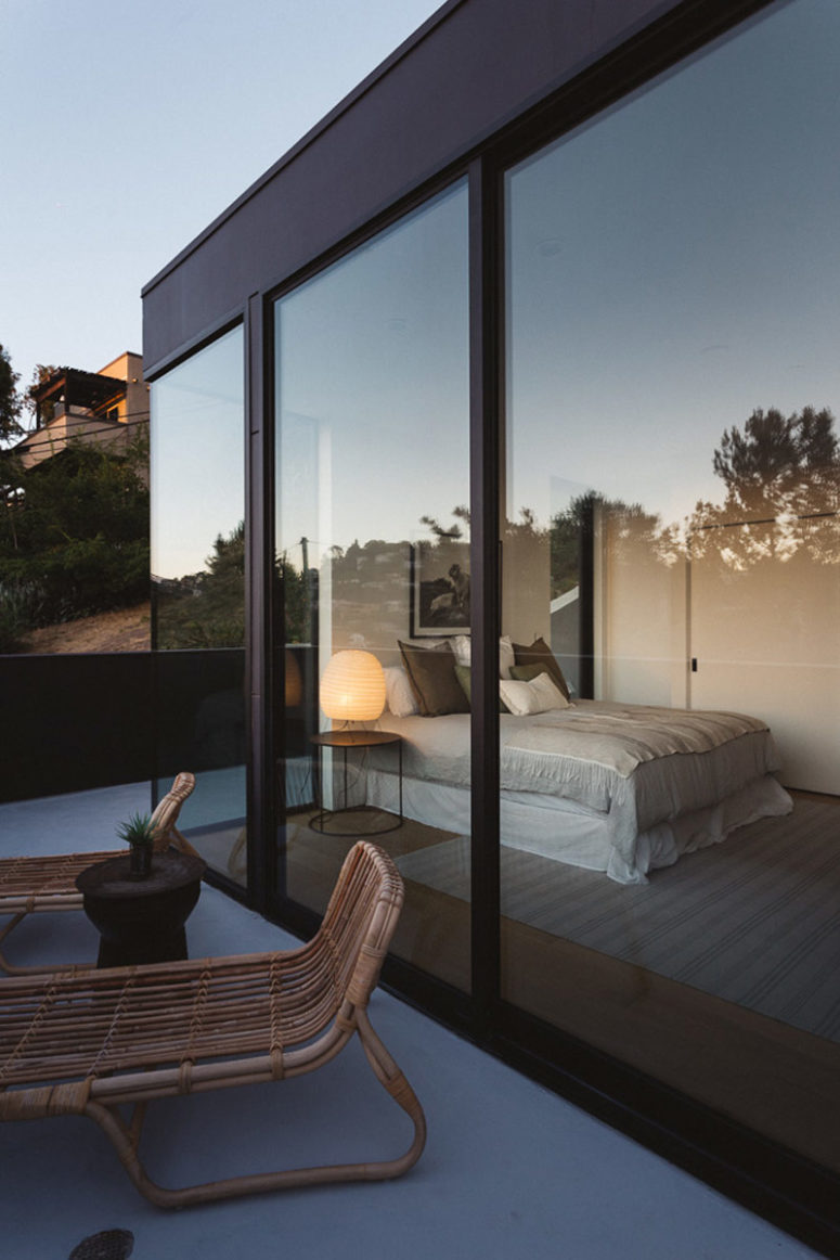 The bedroom has glass walls to connect it to outdoors and fill with light