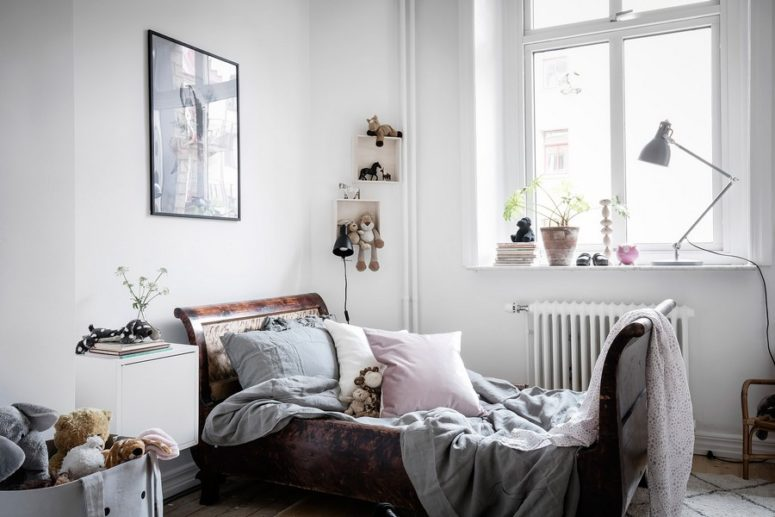 The kid's room features box shelving, a vintage wooden bed and lots of toys