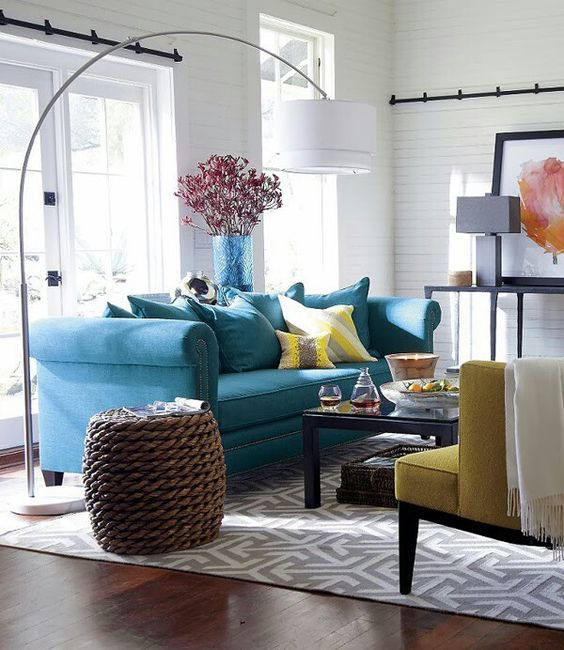 a bold blue sofa and a sunny yellow chair and pillows for a gorgeous coastal room