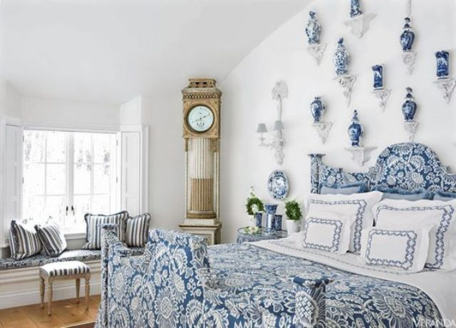 a chic blue bedroom with porcelain vases and a chic vintage clock in the corner