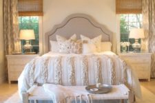 09 a cozy neutral bedroom with a large chandelier and bedside lamps that fit the look of the room