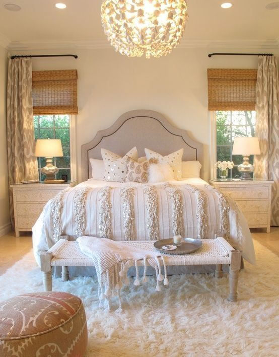 a cozy neutral bedroom with a large chandelier and bedside lamps that fit the look of the room
