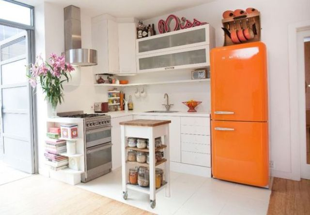 a neutral modern kitchen with a bold orange Smeg fridge for a colorful statement