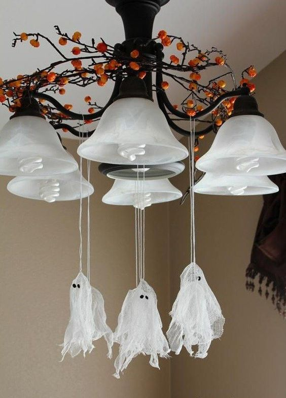 attach small cheesecloth ghosts to the chandelier to give your home a Halloween feel