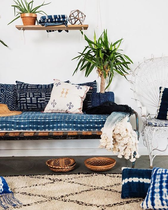 shibori pillows and an upholstered bench add to the look of this boho inspired space