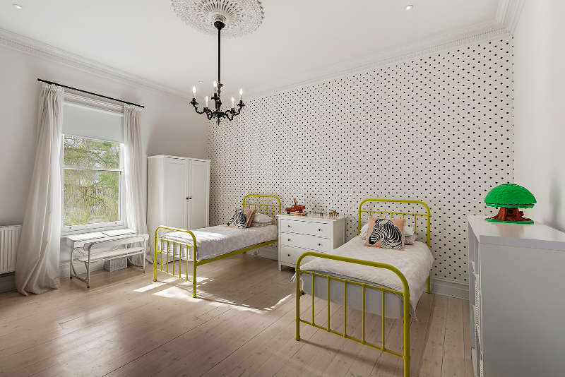 A shared kids' bedroom has vintage beds painted yellow, a study space by the window and a wardrobe