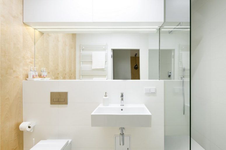 The bathroom is small and done in white and the same wood as everywhere, to connect the space
