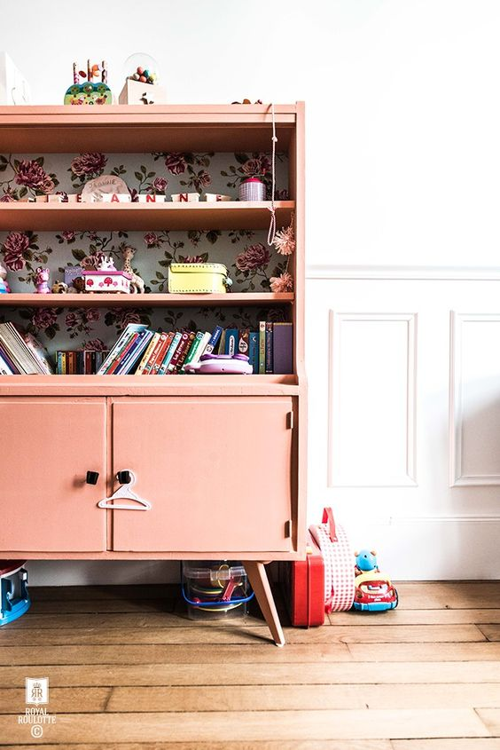 a coral-colored sideboard with shelves and floral wallpaper inside for a kids' room