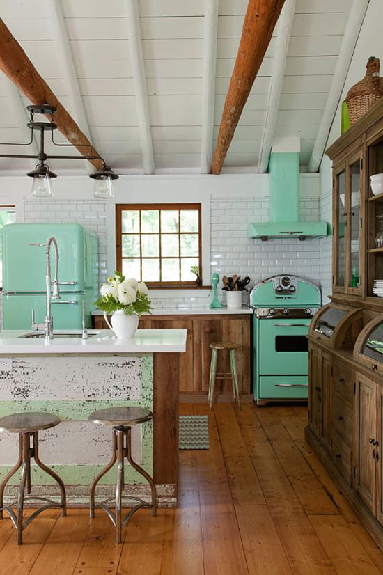 a rustic cottage kitchen is refreshed with a green fridge, cooker and a hood