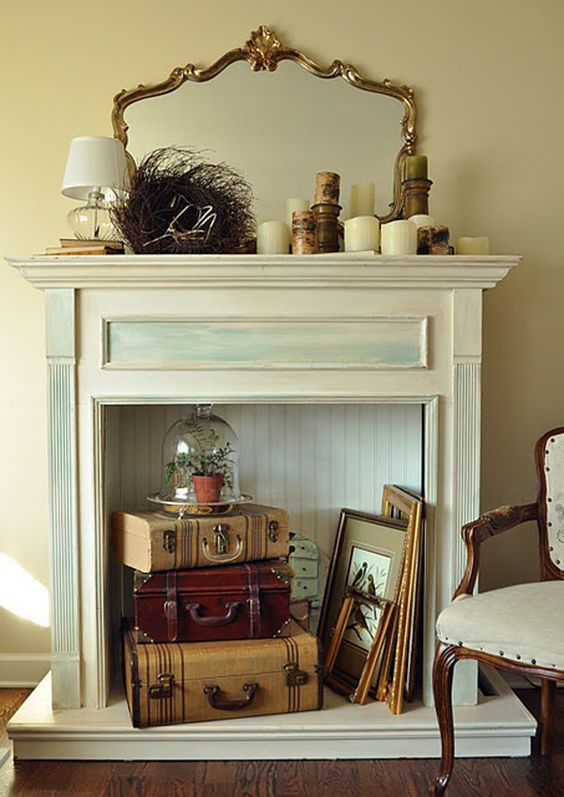 an antique fireplace is used for a vintage-inspired display with suitcases, a cloche piece and paintings