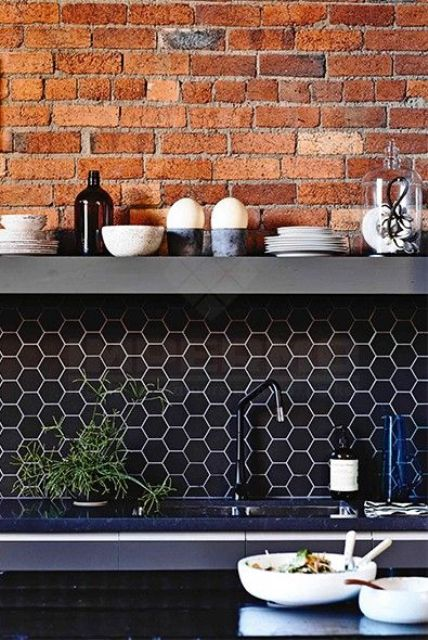 an industrial kitchen with a brick wall, a navy hex tile backsplash and navy countertops