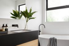 10 large matte black rectangular tiles on the floor and matching ones in white on the wall create a real home spa