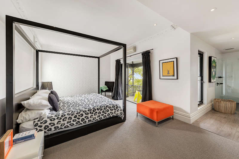 The master bedroom features a framed bed, bold pieces and a balcony to enjoy fresh air