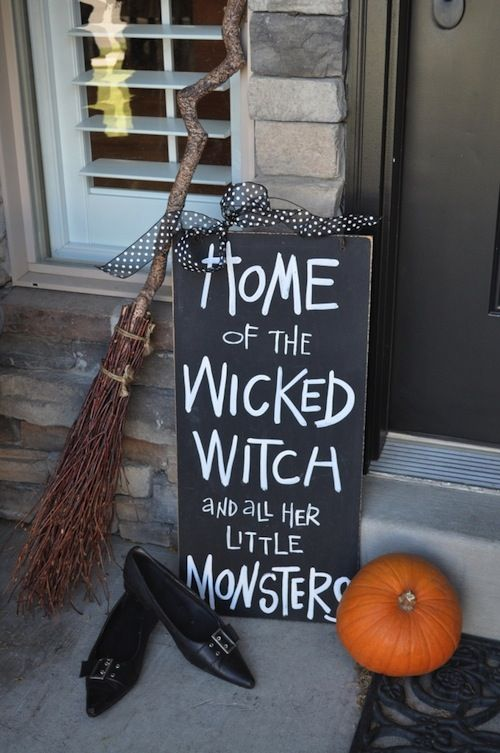 a black and white sign, witch's shoes, a broom and a pumpkin is a nice combo for a porch