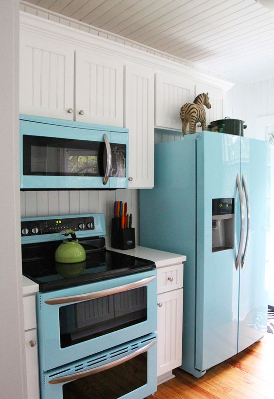 a blue fridge, microwave and cooker spruce up the traditional white kitchen
