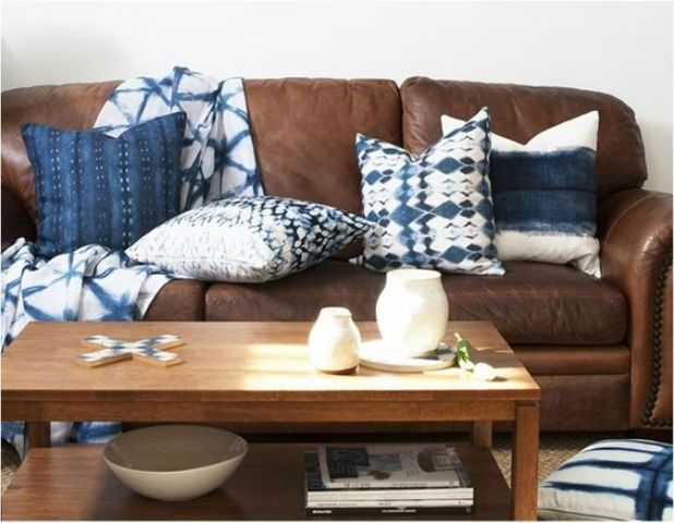 a brown leather sofa looks refreshed and more eye-catchy with shibori pillows and a blanket