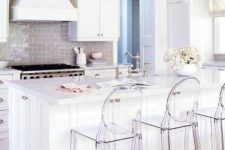 11 an all-white kithen is spruced up with a glossy beige kitchen backsplash and acrylic chairs