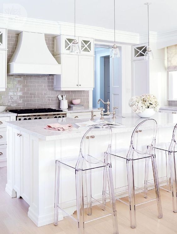 an all-white kithen is spruced up with a glossy beige kitchen backsplash and acrylic chairs