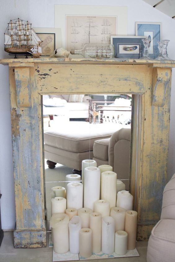 an antique shabby fireplace clad with wood is finished with mirror and some candles