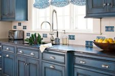 11 blue chalkboard painted cabinets with a vintage design and printed Roman shades