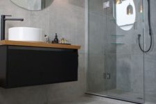11 concrete-looking matte grey tiles cover the whole bathroom and make it modern and refined