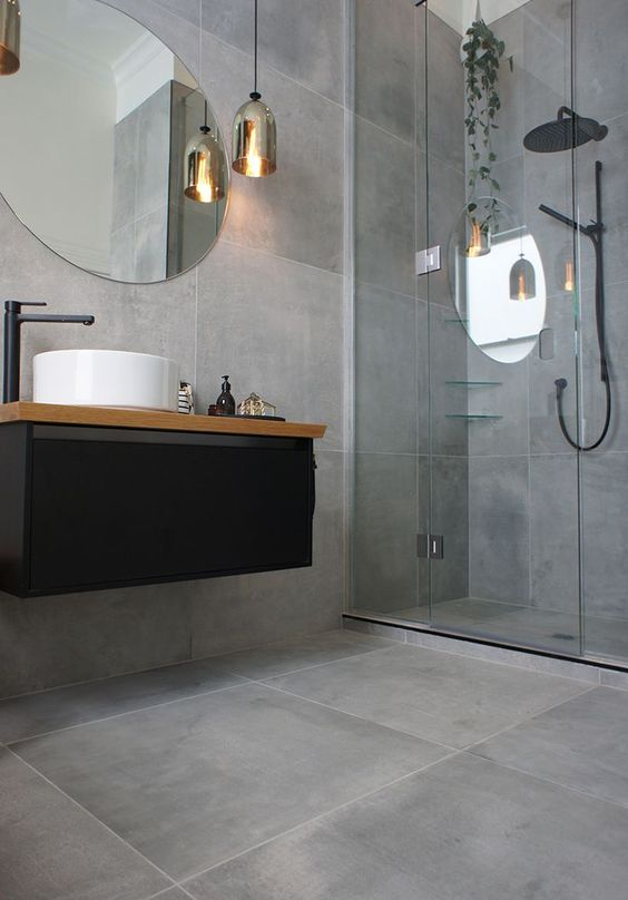 concrete-looking matte grey tiles cover the whole bathroom and make it modern and refined