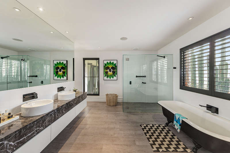 The master bathroom is large, there's a shower, a vintage bathtub and a double bathroom vanit of marble