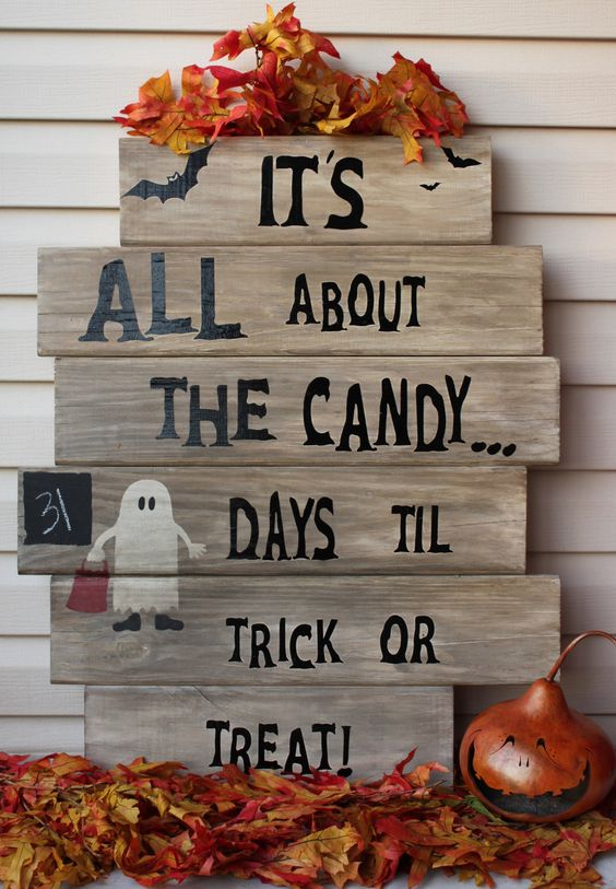 a chic pallet sign with black letters, a painted ghost and faux fall leaves