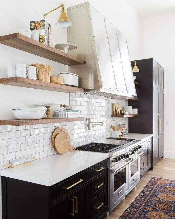 retro inspired black and white kitchen with brass touches, nautral wood and a glossy white backsplash