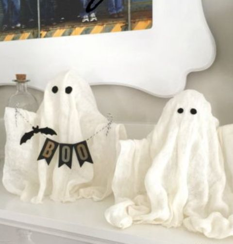 small cheesecloth ghosts with eyes, a banner and a faux bat for mantel decor