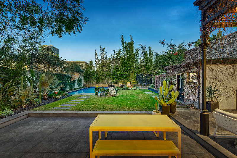 The outdoor space features bold yellow furniture, living walls and a swimming pool