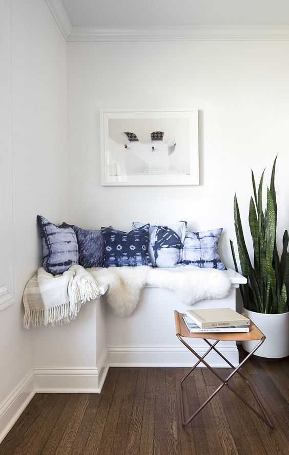 a cozy reading nook is spruced up with shibori pillows and a faux fur cover