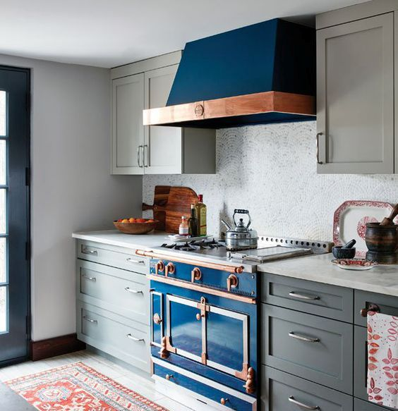 a deep blue kitchen stove with a copper touch and a matching hood in a grey kitchen