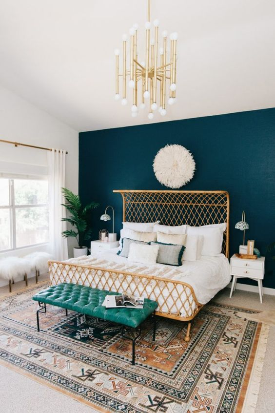 a glam art deco bedroom with a teal statement headboard wall and brass accents