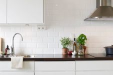 13 glossy white subway tile add interest and shine to a modern sleek kitchen