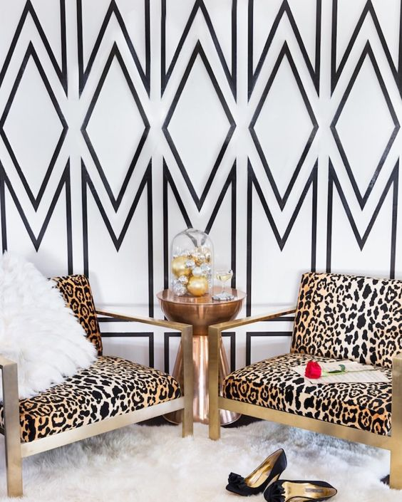 statement geo wallpaper wall and brass cheetah print chairs, a faux fur gur make this nook very glam