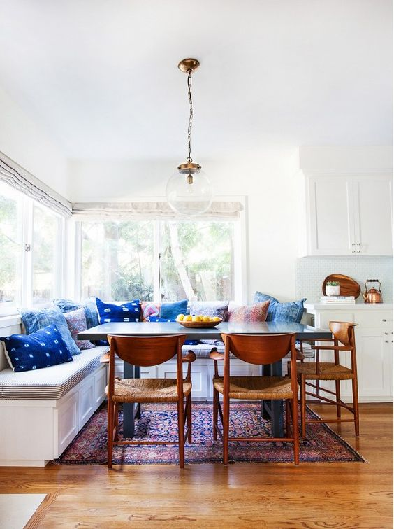 a dining zone spruced up with colorful pillows including shibori ones