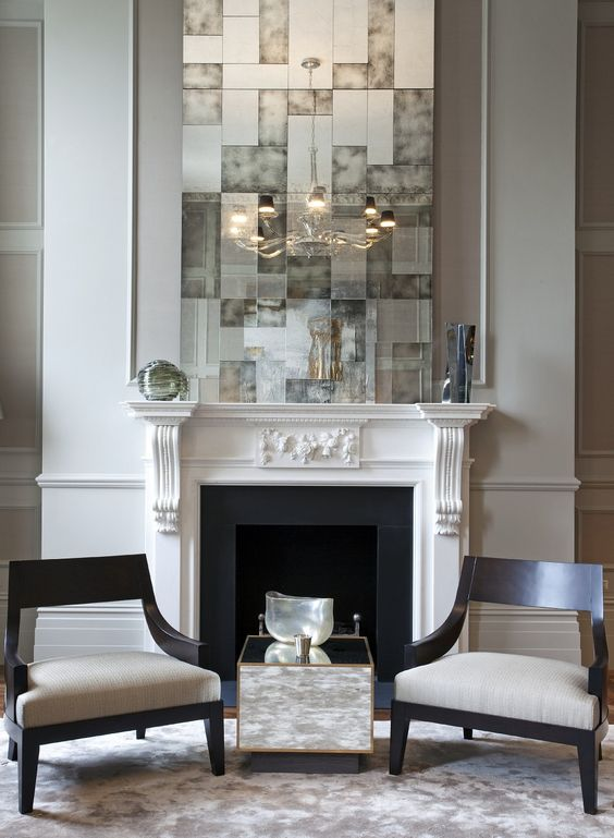 a white vintage fireplace with black inside and firewood on a metal stand just for display