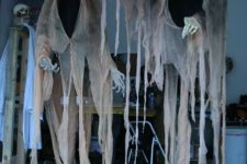14 dark-colored cheesecloth ghosts with a lantern will find a way to your outdoor space