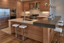 15 a kitchen island with a concrete countertop on the side accentuated with pendant lamps