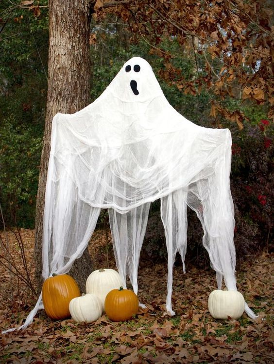 a large cheesecloth ghost with a spooky face and some pumpkins under it